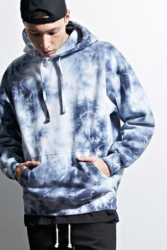 A fleece knit hoodie by EPTM.™ featuring an allover tie dye design, a drawstring neckline, a kangaroo pocket, ribbed trim, and long sleeves.