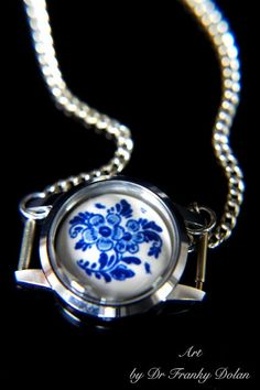 "You will find a perfectly sweet little watch case that houses an antique hand-painted Delft porcelain relic. This little work of art is forever preserved and displayed in the cleverest of frames. People will certainly compliment you on this beautifully unique find! This flowered focal piece measures 1"" x 1.25"", and is held up by a classic 18"" chain. - www.FaeFactory.com"