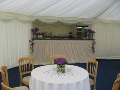 Single purple hydrangeas are used to decorate the bar annexe in this wedding marquee ..