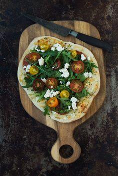Det her er en nem hvid pizza at bage selv. Pizzaen er smørret med ost i stedet for tomatsovs og toppet med rucola, tomat og feta.