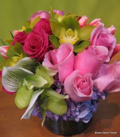 Hot pink roses, dark pink roses, green cymbidium orchids, Lady's Slipper orchids, pink tulips and lavender hydrangea