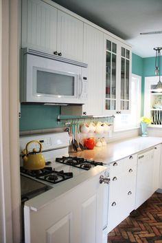 White & turquoise kitchen with silver hardware.  Love this!  Wonder if I could talk my husband into that wall color?