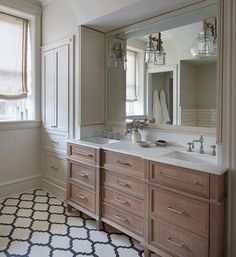 Charming bathroom boasts a brushed oak dual vanity adorning polished nickel pulls and a honed white marble countertop fitted with sink paired with polished nickel hook and spout cross handle faucets located beneath a cream framed vanity mirror flanked by cream paneled medicine cabinets lit by glass bell jar wall sconces.