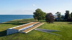 Roger Ferris + Partners has tucked a bar-shaped volume that contains a swimming pool into a grassy hill overlooking a tidal estuary in Connecticut. Indoor Swimming, Swimming Pools, Concrete Retaining Walls, Contemporary Barn, Recessed Ceiling Lights, Hamptons House, Maine House, Pool Houses, Architectural Digest