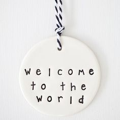 clay gift tag for a new baby gloss glaze on one side with black text write your message on the unglazed side with a felt pen finished with black + white twine approximately 60 mm diameter each caroline c piece is handmade so no two pieces are evr the same