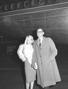 Actress Marilyn Monroe is accompanied by her husband, playwright Arthur Miller, as she arrives at International Airport from New York to start work on a 20th Century-Fox picture. (Publication: Los Angeles Times - Publication date: November 4, 1959)