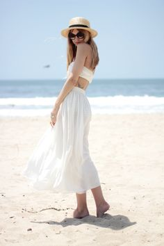 If you're spending the day at the beach take a cue from Liz and style a bathing suit top with a high waisted flowy skirt, funky sunglasses, and a straw hat.