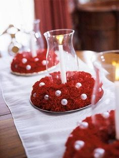 Carnation Centerpieces - these 3 wreaths are  easy to make with florist's foam wreath bases, pearl ornaments, and scarlet carnations. Add glass hurricanes and ivory-color candles for classic Christmas centerpieces.