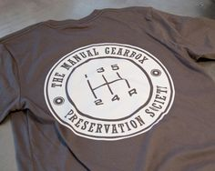 """The official Manual Gearbox Preservation Society Insignia t-shirt. Show your love for the unparalleled experience of the manual gearbox, and become an official member of T.M.G.P.S! 3.5"""" insignia on th"""