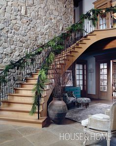 Grand as it is, this wrought-iron staircase still benefits from a touch of nature come the cooler months. | Photographer: Michael Graydon | Designer: Barbara Purdy