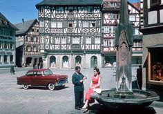 1957 Opel Olympia Rekord I'm not sure about the location of this photo, but I have a feeling it could be Rothenburg ob der Tauber. This is a 1957 Opel Olympia Rekord, so this photo is probably used for the 1958 calander. Please note how the car and the lady's dress are about the only items with real color here. The fountain doesn't look to be in a very fine shape too. Wirtschaftswunder or not, Germany in the 1950s was still recovering of the hardships inflicted by the Nazi regim...