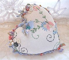 Heart pillow .....embroidered old bureau scarf that I made into a pillow .  vintage buttons and pearls.  twisted and knotted fabric on the edges