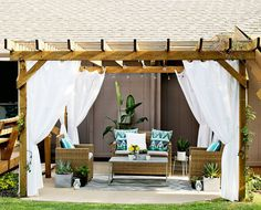 Pergola with curtains for privacy, comfy furniture, lovely pops of color, plenty of flowers: charming personal retreat!