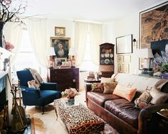 Living Room Photo - A leather couch paired with a blue armchair and a leopard-print ottoman
