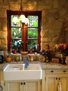 The stone wall, wood window and farmhouse sink with granite counter all give it an old world, French country feel.