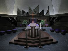 The North Christian Church in Columbus, Indiana, designed by Finnish-American architect Eero Saarinen and completed in 1964.     The building is hexagonal, with a central spire 192 feet high. Below the spire, an oculus that admits light into the main level. The sanctuary is located at the center of the building, with the altar located in the center of the sanctuary. Rows of pews surround the altar in a hexagon, reflecting the idea that worship should be a central aspect of congregational lif...