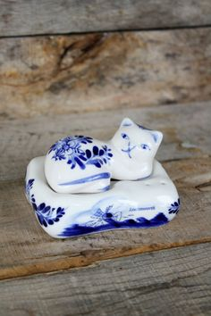 Sweet vintage salt and pepper set features a ceramic cat sitting on its bed. Hand painted in traditional delft blue and white. Made in
