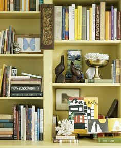 Animal Attraction- figurines.    In smaller doses, figurines like this pair of birds add a fun decorative element, as does the framed butterfly acting as a bookend on this styled bookcase.     Eclectically decorated bookcase. Cute idea.
