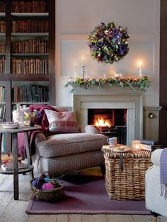 Decorative fireplace, wreath above, warm blanket and a pillow on the couch.