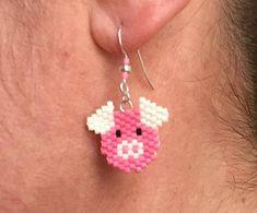Boucles doreille réalisées à la main en tissage brick stitch avec des perles Miyuki roses, blanches et noires en forme de tête de cochon. Crochets américains en métal argenté agrémentés de perles Miyuki et petites perles argentées. La longueur des boucles doreilles est denviron