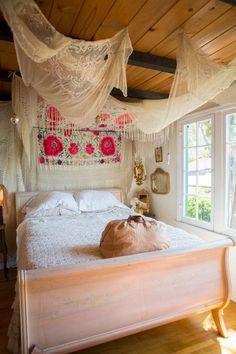 chambre adulte de style bohème avec ciel de lit semi-transparent et déco murale canevas