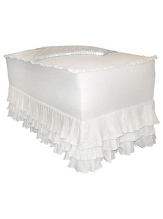 white slipcovered trunk/bench. DIY this without ruffle/padded top bit. Use white linen similar simple design as white cotton organza curtain. Cover navy trunk of books to lighten it up, simple shabby chic