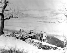 Two soldiers gaze across the Yalu River to the mountains of Manchuria. A temple and bridge set on fire by the Air Force, still burn in the valley below. They are just outside the city of Hyesanjin, Korea.