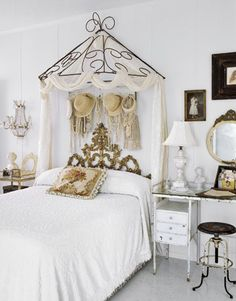 Feminine Details  An ornate gold headboard is enhanced by a canopy from an old store display, draped with white fabric. Hanging below are vintage pearls, beads, hats, and bags