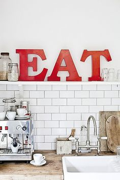kitchen in red and white with EAT typography Please visit for more information