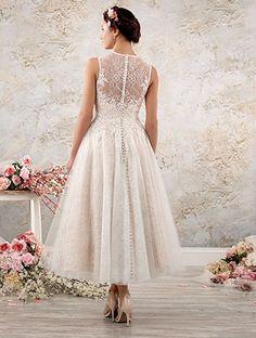 A tea length shabby chic wedding dress with a sleeveless sheer yoke, sweetheart neckline, and full, swinging lace skirt.