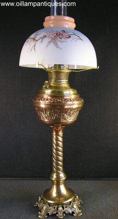 This kerosene banquet lamp has a copper finish on the foot, stem and vase. The stencil and hand painted dome shade, also called a half shade, is from the same period as the kerosene banquet lamp but it is impossible to say if it is original to the lamp.