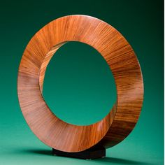"""""""Eye Of The Storm"""" 30"""" High Wood: Bubinga Although the cross-section of this sculpture is a triangle, the addition of a 1/3 twist in the ring causes there to be only one side to the piece. There are 192 pieces of wood in the sculpture."""