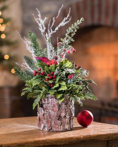 """{$tab:description} Set your table in style Add a touch of the winter woods to your decor with holly, pine, and wispy twigs arranged in a faux bark planter enlivened with a red cardinal on a cozy perch. {$tab:DETAILS}  16"""" Height x 12"""" Width Faux Bark Planter - 5""""H x 5""""Diameter Wonderful, Wispy, & Woodland Arrives Fully Shaped & Ready to Display Designed and Assembled in the USA Petals Exclusive       {$tab:SHIPPING & RETURNS} Standard Ship..."""