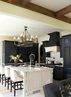 Like the finish diamond trim on the side of the island.  black kitchen cabinets and white island. Comfortable stools.