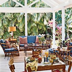Classic Throwback    On the porch, a pavilion-like roof shelters an outdoor living area complete with sofa, armchairs, and a rug. The vintage Heywood-Wakefield bamboo furniture set feels crisply shipshape with cushions covered in marine-blue fabric and white piping