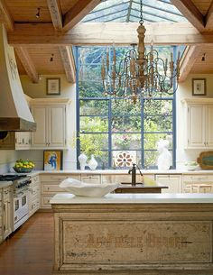Stylish Islands for Traditional Kitchens - Traditional Home® Skylight vaulted ceiling, old world style, exposed wood ceiling, reclaimed oak beams, white cabinets, chandelier. greenhouse-style glass ceiling and steel-framed windows, make this kitchen feel like one with the outdoors. French limestone counters, heart-pine floors, and painted cabinets enhance the kitchen's warm traditional appeal. Architect for renovation: Robbin Hayne Interior designer: Ann Runyon Carter