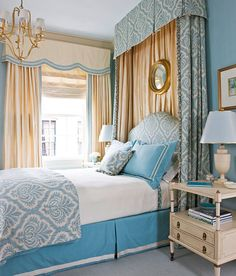 """Serene Blue & Gold Bedroom  Designer  Kelley Proxmire used 150 yards of luxurious fabric and trim to create a space  for the D.C. Design House that is """"warm, welcoming, and enveloping."""" The  bedroom's centerpiece is the upholstered headboard tucked into billowing canopy  treatment. The playful robin's-egg-and-ivory pattern ties the pillows, linens,  and bedskirt together."""