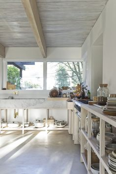 light wood cabinets with white marble counters. clean lines and sil on kitchen window in front of sink