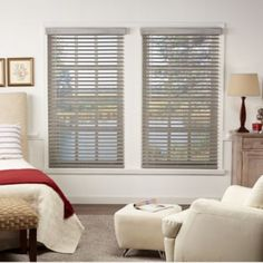 Windows with gray allen + roth blinds on a white wall.