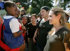 Angelina Jolie and Brad Pitt are introduced to a Haitian schoolgirl by Haitian-born hip-hop musician Wyclef Jean, second from left, at the Immaculate Conception School, in Port au Prince, Haiti, Friday, Jan. 13, 2006. (AP Photo/Brennan Linsley)