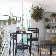 Een balkon met een witte parasol, een grijze ronde tafel, stoelen en kruk en een wit windscherm/zonnescherm. Ikea.