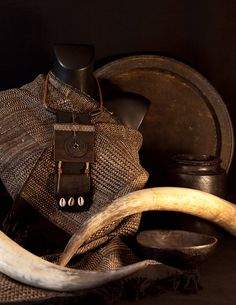A surprising piece at the crossroads of Africa and Asia! The first large square piece is made of recycled thick leather (industrial machine belt ) decorated with a ribbon and an old Chinese bronze coin. Below,hangs a piece of black ebony decorated with 3 cowries shells.