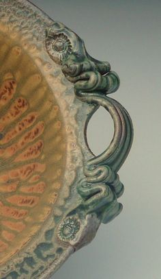 """Great take on a colander. Rinse, strain, and serve your favorite fruits, vegetables, and pasta too! (The separate saucer keeps water away from your counter top or table) Hand-thrown stoneware; glazed with durable and rich green and golden ash glazes. Reduction fired to 2360 degrees F. Approximately; 10½"""" diameter (including handle) x 5"""" height. Dishwasher and microwave safe too. Because each individual piece of pottery I create is unique, it is unlikely to exactly match the published image…"""