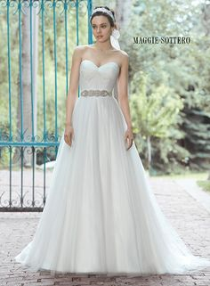 Tulle ballgown with a delicate ruched bodice and detachable grosgrain ribbon belt. Available with Swarovski crystal belt. Florence by Maggie Sottero.