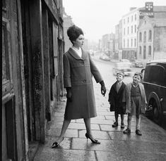 American model Linda Ward (O'Reilly) posing, while two local boys give her outfit the once over … Date: Some time after January 1960 to Winetavern Street, Dublin, Ireland. Susan Sontag, Vintage Street Fashion, 1960s Fashion, Irish Fashion, Fashion History, West Side Story, Fashion Catalogue, Mode Vintage, Modeling Poses