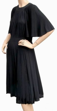 Age: 1960s Label: Jean Muir Paris Retailer's Label: Hilde Originals Montreal Color: Black Material: Silk Jersey Description: This wonderful dress features cape-like sleeves and pleating across the cen