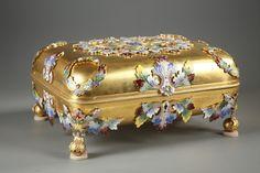 """Importante coffret en bronze doré et émail champlevé avec sa clef soutenue par quatre pieds boule. Le couvercle et la boîte sont gravés sur toute leur surface de couronnes, feuilles d'acanthes et feuillages polychromes. Sur le rebord, une armoirie appliquée ultérieurement avec l'inscription en latin: """"Lilium inter spinas"""" marquée sur un ruban surmonté par deux médaillons avec des symboles héraldiques et une couronne flanqués par un lion et un aigle ailés.Circa : 1900Dim: L:26cm, P:20cm…"""