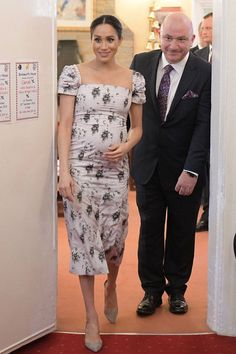 While at Meghan Markle and Prince Harry's first joint public engagement of in Birkenhead, the Duchess of Sussex donned a violet purple dress and cherry red. Estilo Meghan Markle, Meghan Markle Style, Meghan Markle Prince Harry, Prince Harry And Megan, Princess Meghan, Princess Diana, Maternity Fashion, Maternity Dresses, Maternity Clothing