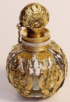 English Bulbous Cage Work Scent Flask, Circa 1760 Gold cage work scent flask with chained shell stopper and French inscription around neck 2 inches high.