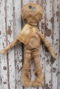 """Raggedy Mummy Doll -  This Raggedy Mummy was made by using a pattern from Homespun Primitives. He's made of muslin material that has been stained and baked to give it a nice prim look. And smells YUMMY! I've wrapped him up in coffee stained cheesecloth. He has button eyes and a prim tag that reads """"Raggedy Mummy."""" He measures approx. 16 inches tall."""